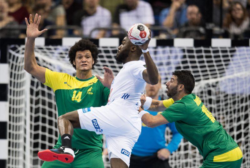 Thiagus Petrus (14) e Felipe Borges, da seleção brasileira, tentem bloquear arremesso do francês N'Guressan, pelo Mundial de handebol (Crédito: Soeren Stache / DPA / AFP)