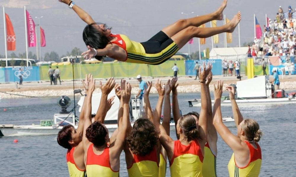 Elisabeta Lipa Oleniuc sendo jogada para cima por sua equipe romena após medalha no remo em Atenas 2004 (Reprodução)
