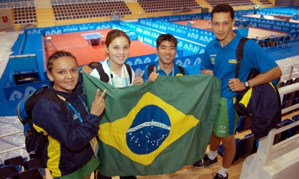 Mesatenistas com a bandeira brasileira em Atenas-2004: Ligia Silva, Mariany Nonaka, Hugo Hanashiro e Thiago Monteiro